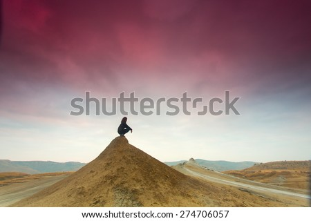 Silhouette of woman meditating on top of a hill - stock photo