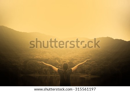 Silhouette of woman on a summit with upraised arms on the top mountain with the sunset, Praise for GOD. - stock photo