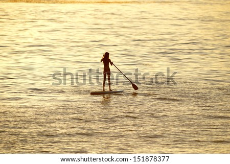 silhouette of woman paddleboarding at sunset, malibu, california, recreation sport paddling ocean beach surf - stock photo