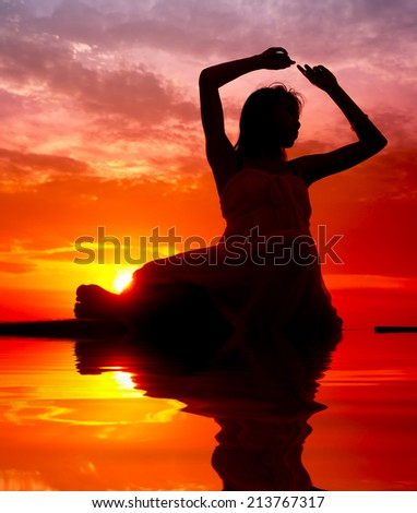 Silhouette of woman performs as a dancer during sunset   - stock photo