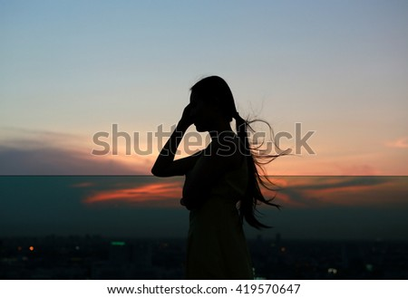 Silhouette of woman relax at sunset on rooftop of the building - stock photo