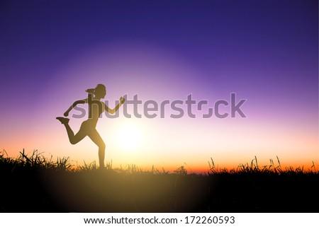 Silhouette of woman running alone at beautiful sunset  - stock photo