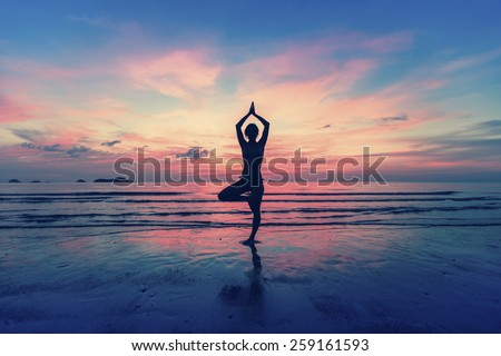 Silhouette of woman standing at yoga pose on the beach during an amazing sunset. - stock photo