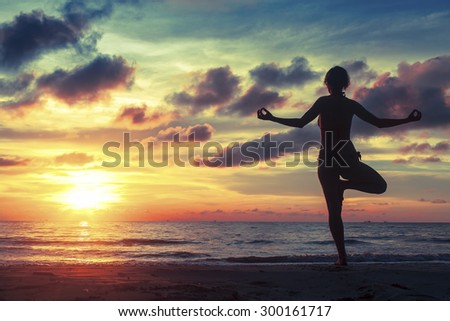 Silhouette of woman standing at yoga pose on the ocean beach during an fantastic sunset. - stock photo