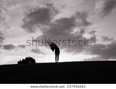 Silhouette of woman stretching - stock photo