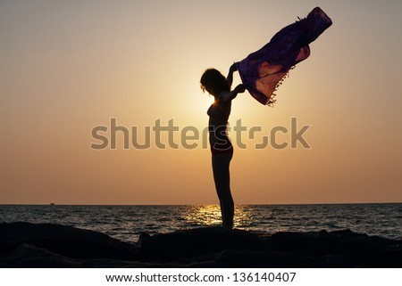 Silhouette of woman that stands against sunset sun at the seashore and waves with her pareo - stock photo