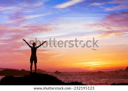 silhouette of woman with raised hands on beautiful sunset background - stock photo