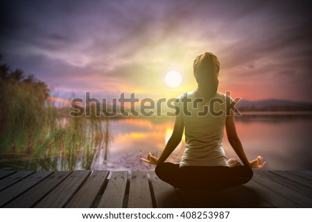 Silhouette of woman yoga pose and meditation on the wooden bridge over lake view at the sunset in the evening. Image create for business, healthcare, sport and lifestyle of people. - stock photo