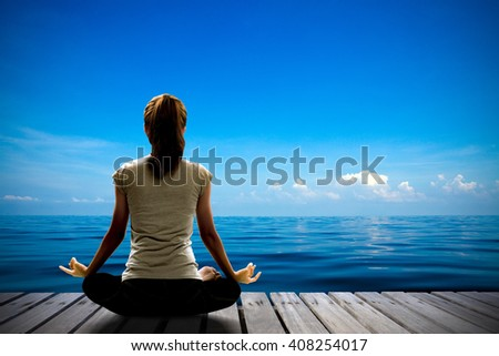 Silhouette of woman yoga pose and meditation on the wooden bridge over the blue sea and blue sky. Image create for business, healthcare, sport and lifestyle of people. - stock photo