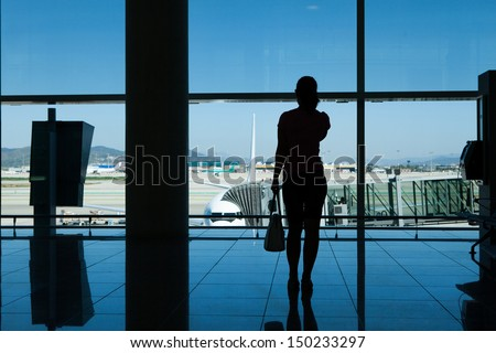 Silhouette of women talking on cell phone in airport terminal - stock photo