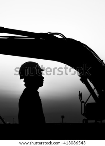 Silhouette of  worker at construction site - excavator loader in the background - oilfield - black and white - stock photo