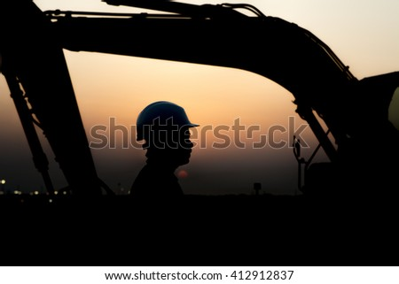 Silhouette of worker at construction site in oilfield. heavy equipment background - sunset  - stock photo