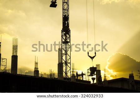 silhouette of worker working with crane for construction - stock photo