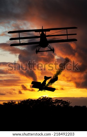 Silhouette of WWI plane shooting down another one at sunset. (Artist impression) - stock photo
