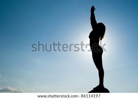 Silhouette of Yoga at summit with sunlight and Blue sky. - stock photo