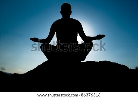 Silhouette of Yoga at summit. Young adult at the top of summit with aerial view of the blue sky - stock photo