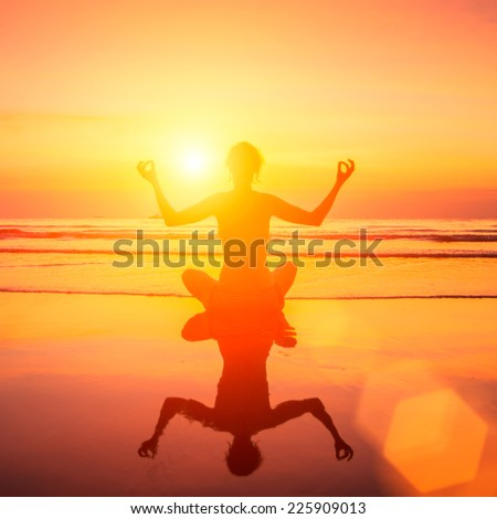Silhouette of yoga woman on sea sunset with reflection in water. - stock photo