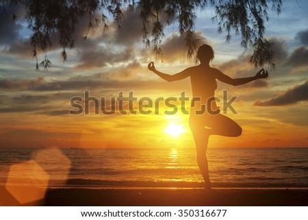 Silhouette of yoga woman standing on the beach during an sunset. - stock photo