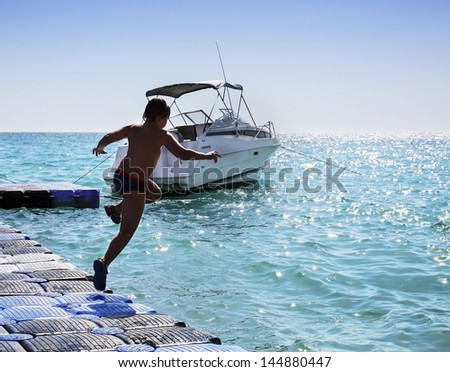 Silhouette of young boy jumping into the sea from pier - stock photo