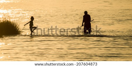 Silhouette of young child playing in the shallow waters of the Indian River Inlet (Delaware) with a family member clamming nearby as the sunsets. - stock photo