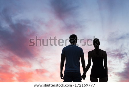 Silhouette of young couple holding hands looking at the sunset - stock photo