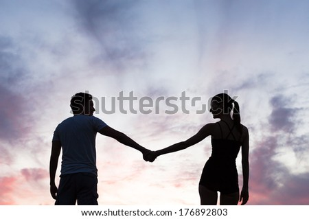 Silhouette of young couple in love holding hands. - stock photo