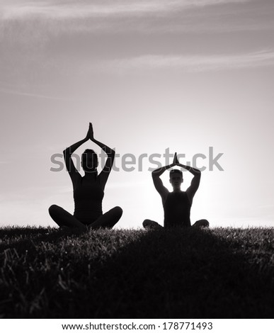 Silhouette of young couple meditating. - stock photo