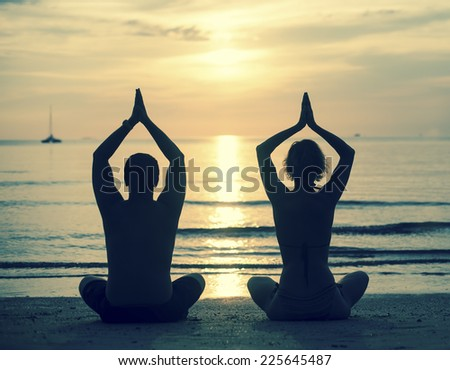 Silhouette of young couple practicing yoga on sea beach during sunset. Cross-process photo style. - stock photo