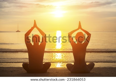 Silhouette of young couple practicing yoga on the beach during sunset. - stock photo