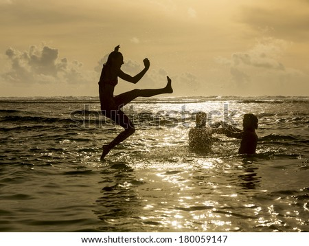 Silhouette of young girl jumping out of the ocean, which throws strong two man on the background of the expiring sunset - stock photo