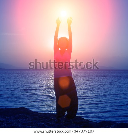 Silhouette of young girl standing on the beach with hands up, at the sunset against the sun - stock photo