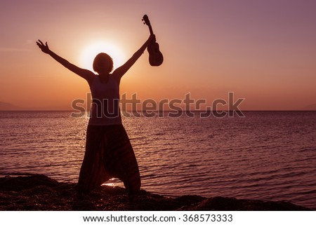 Silhouette of young girl standing on the beach with hands up, with ukulele, at the sunset against the sun - stock photo
