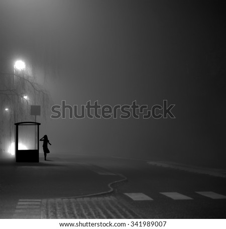 Silhouette of young girl waiting for bus by shelter on dark foggy evening - stock photo