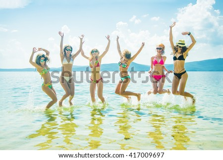 Silhouette of young group of people jumping in ocean at sunset Team of adult girl jump in water on summer beach against blue sky with clouds Water splash Hair fly in air Empty space for inscription - stock photo
