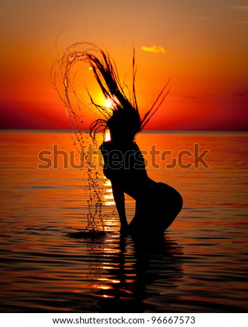 Silhouette of young lady on a beach on sunset background - stock photo