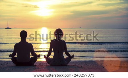 Silhouette of young man and woman practicing yoga in the lotus position on the ocean beach during amazing sunset. - stock photo