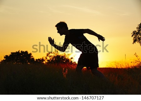 Silhouette of young man at the sunset - back lit  - stock photo