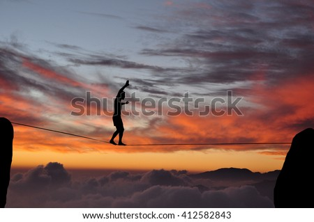 Silhouette of young man balancing on slackline high above clouds and mountains during sunset. Slackliner balancing on tightrope between two rocks sun and clouds behind, highline silhouette. - stock photo