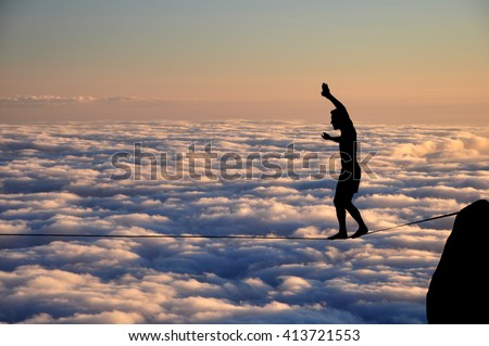 Silhouette of young man balancing on slackline high above clouds. Slackliner balancing on tightrope beautiful colorful sky and clouds behind, highline silhouette. - stock photo