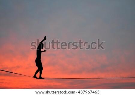 Silhouette of young man balancing on slackline, sun and clouds behind. Slackliner balancing on tightrope during sunset, highline silhouette. - stock photo