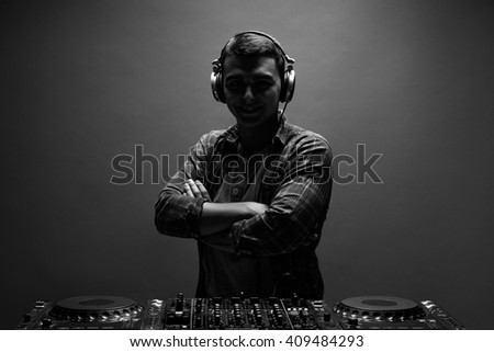 Silhouette of young man, dj with mixer. Back and white photo. - stock photo