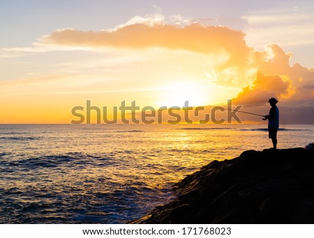Silhouette of young man fishing during sunset - stock photo