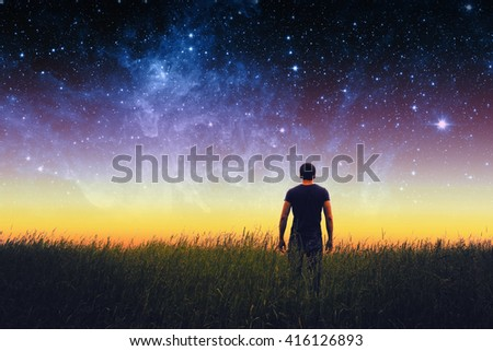 Silhouette of young man on stars sky. Elements of this image furnished by NASA. - stock photo