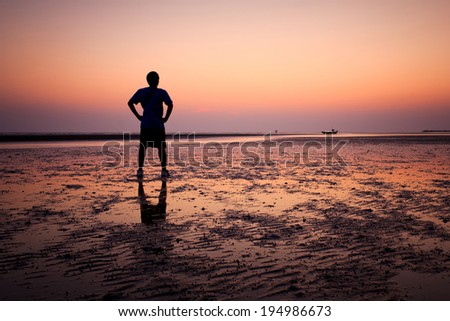 Silhouette of young man on the beach at sunset  - stock photo