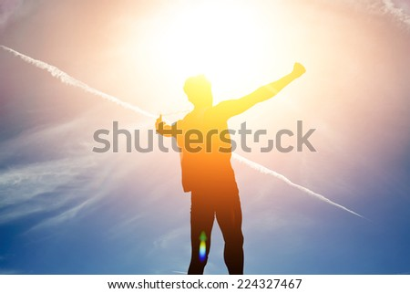Silhouette of young man rejoicing achievement raised the hands, person has attained the goal, concept victory over self, silhouette man exploded to the top hill - stock photo