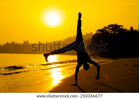 silhouette of young man standing on his hands taken in sri-lanka on the sunrise - stock photo