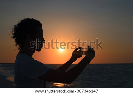 Silhouette of young man taking photo of sunset at seaside with his smart-phone - stock photo