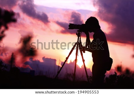 Silhouette of young photographer at sunrise - stock photo