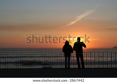 Silhouette of young romantic couple in sunset - stock photo