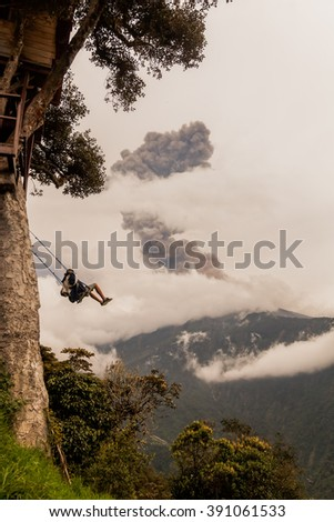 Silhouette Of Young Teenager Man On A Swing, Casa Del Arbol, The Tree House, Tungurahua Volcano Explosion On March 2016 In The Background, Ecuador, South America  - stock photo